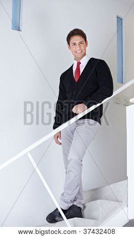Happy attractive business man standing on stairs in the office