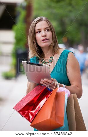 Woman shopping in city with digital tablet