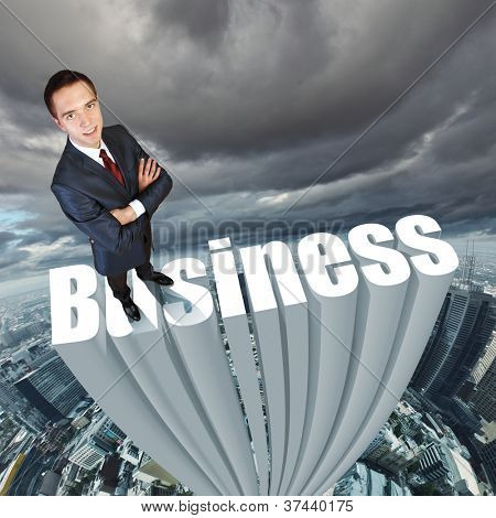 Businessman in suit standing on the word Business