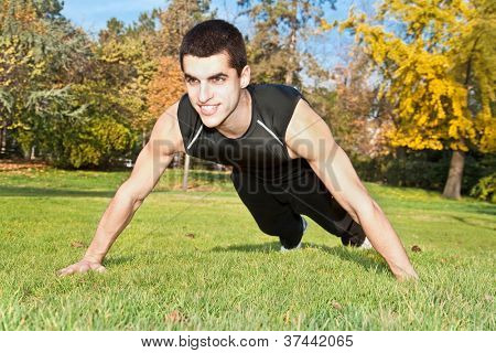 Attractive young man doing exercise in autumn park