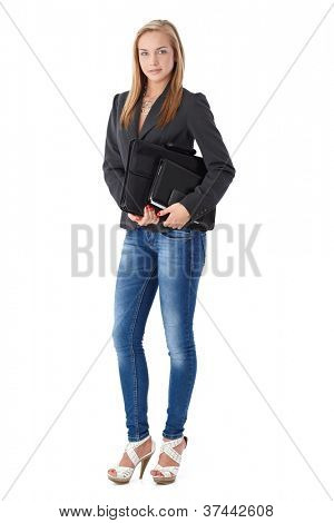 Casual business portrait of young businesswoman with briefcase and organizer, posing in studio, full length.