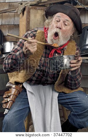Hungry Old Cowboy Eating Beans From A Saucepan