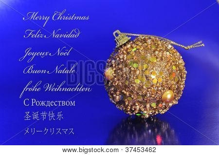a golden christmas ball on a blue background and the sentence merry christmas written in english, spanish, french, italian, german, russian, chinese and japanese