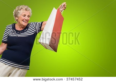 Happy Senior Woman Looking At Shopping Bags Isolated Over green Background