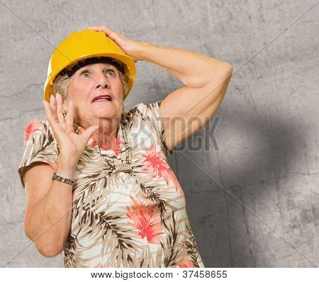Afraid Senior Woman Wearing Hardhat Standing In Front Of Wall