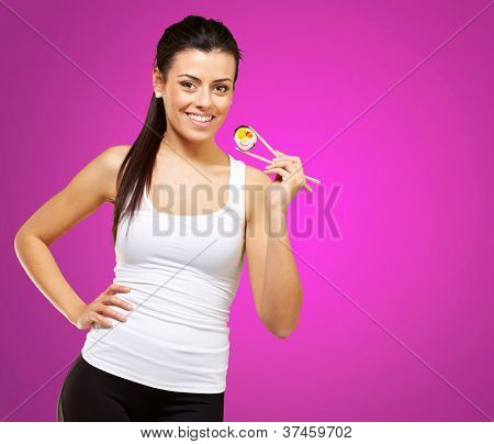 young woman holding a piece of sushi with chopsticks against a pink background