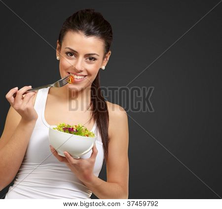 Young woman holding and eating salad on black background