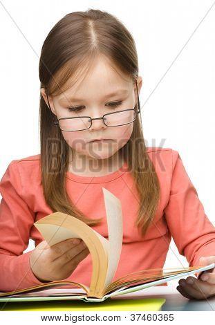 Niedliche kleine Mädchen mit Brille, isolated over White Buch zu lesen