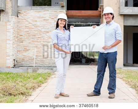 Architects holding banner in a construction site