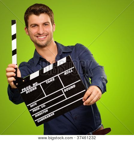 A Young Man Holding A Clapboard On Green Background