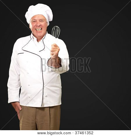 Portrait Of A Senior Male Chef Holding A Beater On Black Background