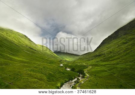 River flowing through a valley in the scottish highlands, the mountains are covered in clouds