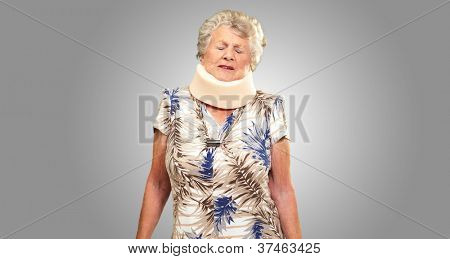 A Senior Woman Wearing A Neck brace On gray Background