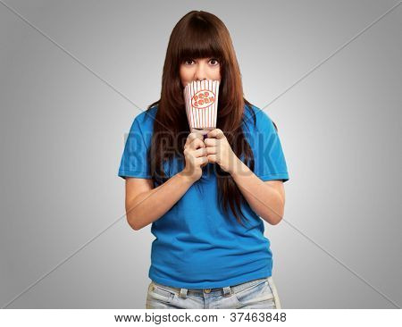 girl looking through empty popcorn packet isolated on gray background