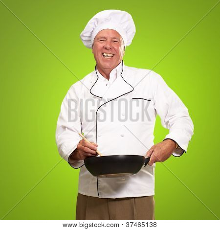 Male Chef Stirring A Non Stick Pan On A Green Background