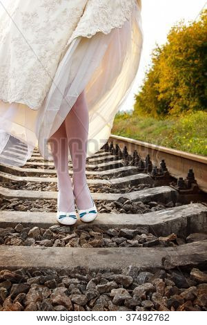 young woman bride's walks on the railway, summer nature outdoor, legs closeup