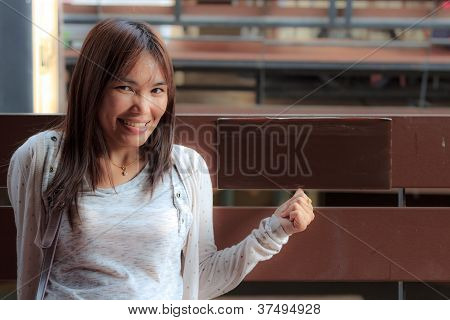 Smile Asian Woman Sit On Chair.