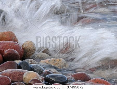 Water splashing against rocks on lake shore