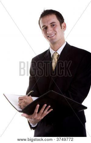 Young Businessman In Suit Writing In Notebook