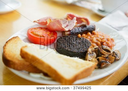 Plate with Full Scottish breakfast containing  toasts, fried eggs, baked beans, grilled black pudding, sausage, tomato,  mushrooms and bacon