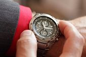 foto of wrist  - Businessman checking the time on his wrist watch - JPG