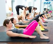 foto of personal care  - Aerobic Pilates personal trainer in a gym group class in a row - JPG