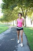 stock photo of workout-women  - A young pretty african american woman jogging in the park - JPG