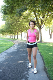 image of workout-women  - A young pretty african american woman jogging in the park - JPG