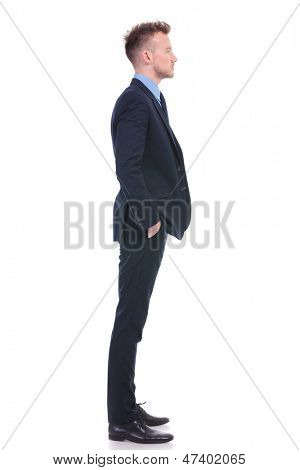 full length side view picture of a young business man standing with his hands in his pockets and looking forward. on white background