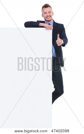 full length picture of a young business man holding a big empty pannel and the thumb up gesture while smiling at the camera. on white background