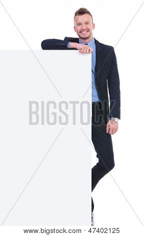 full length picture of a young business man with a big empty pannel smiling at the camera. on white background