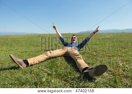 casual young man laying in the grass on a field and cheering with hands in air while screaming and looking at the camera