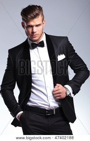 portrait of an elegant young fashion man in tuxedo holding a hand in his pocket and the other on his unbuttoned jacket while looking at the camera. on gray background