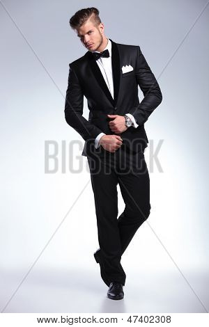 full length photo of an elegant young fashion man in tuxedo looking at the camera while holding his hands on his jacket. on gray background