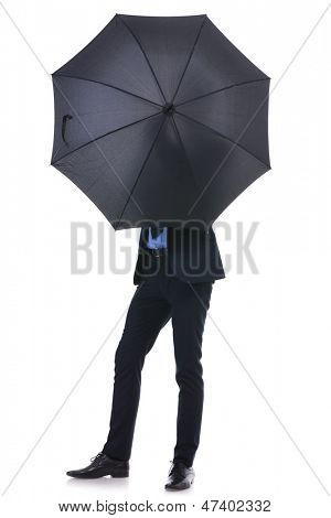 full length picture of a young business man hiding his face behind an opened umbrella. on white background