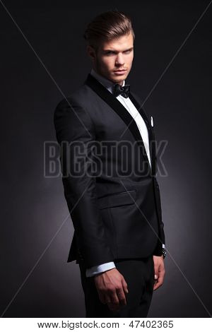 semi profile picture of an elegant young fashion man in tuxedo looking at the camera and frowning. on black background