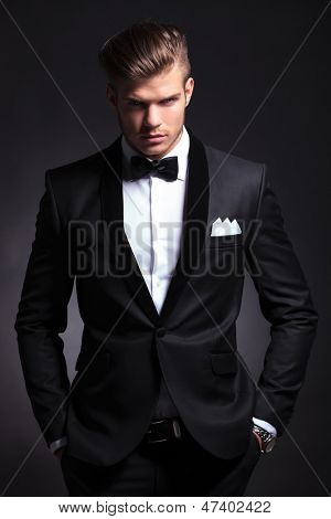elegant young fashion man in tuxedo is holding both hands in his his pockets and looking at the camera.on black background