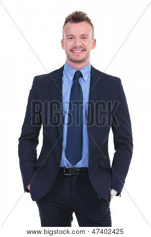 young business man with hands in pockets smiles for the camera. on white background