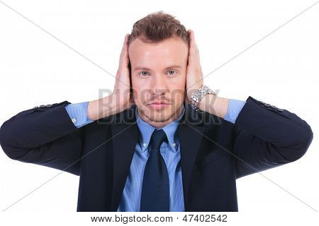 young business man covering his ears with his hands. hear no evil. on white background