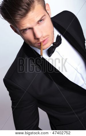 high angle view of an elegant young fashion man in tuxedo holding a lit cigar in his mouth while looking at the camera. on gray background