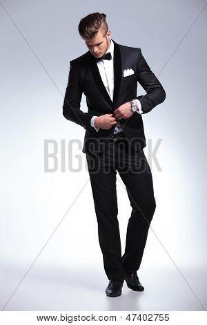 full length picture of an elegant young fashion man in tuxedo buttoning his jacket while looking down, away from the camera. on gray background