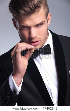 closeup of an elegant young fashion man in tuxedo looking at the camera while preparing to take a smoke from his cigar. on gray background