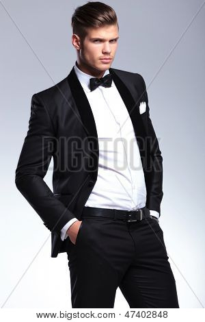 elegant young fashion man in unbuttoned tuxedo holding his hands in his pockets while looking at the camera. on gray background