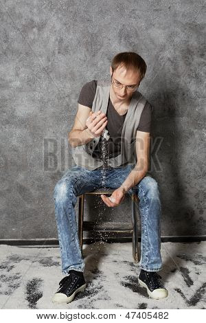 Young man sits on chair in empty room powdered with snow and intersperses snow from one hand to another