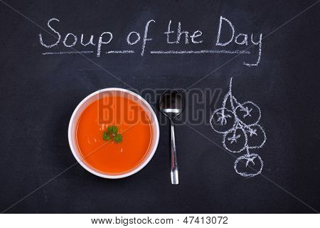 Chalkboard advertising the soup of the day, with a bowl of tomato soup and spoon, garnished with parsley, with chalk drawn tomatoes on the side