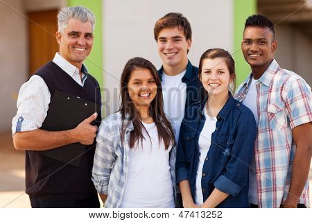 cheerful male high school teacher standing with students outdoors