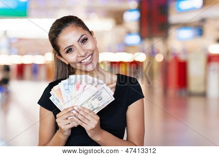 attractive young woman holding cash outside casino