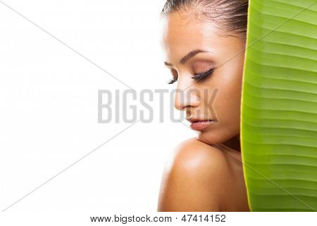 beautiful young woman with eyes closed behind large green leaf over white background