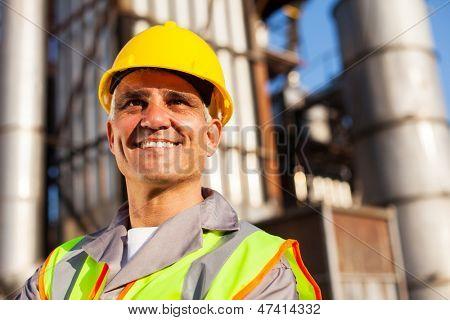 senior fuel refinery worker closeup portrait inside plant