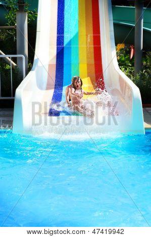 Little Girl On A Waterslide In Aquapark.
